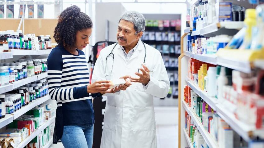 Shot of a pharmacist assisting a young woman in a chemist.
