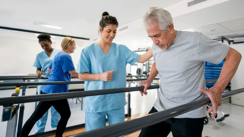 Diverse team of physiotherapist helping senior patients walk between parallel bars all looking happy and smiling.