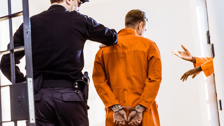back view of prison guard leading criminal in handcuffs.