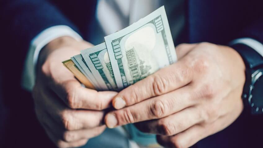Close up, of male hands counting dollar bills, filtered image, business man working financial adviser and counting money banknotes.