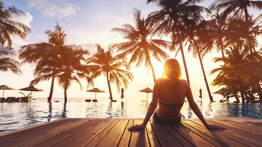 Woman enjoying vacation holidays at luxurious beachfront hotel resort with swimming pool and tropical lansdcape near the beach.