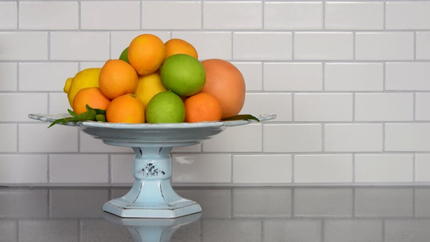 Homegrown selection of citrus fruit in retro modern kitchen with white ceramic subway tile backsplash and quartz countertop.