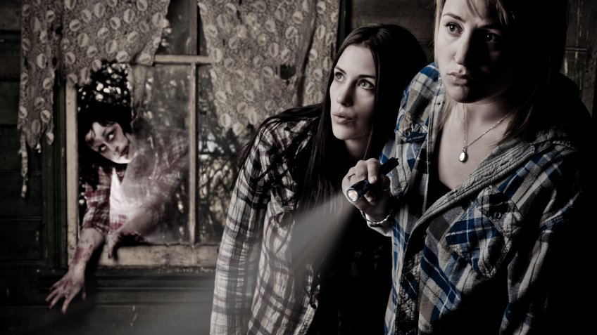 two girls in haunted house with scary zombie