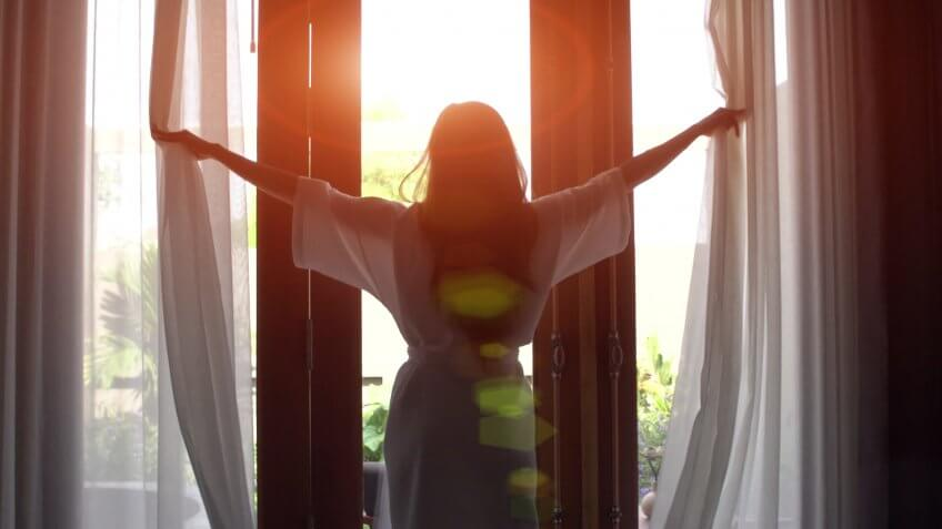 Young woman in bathrobe open curtains and stretch standing near the window at home.