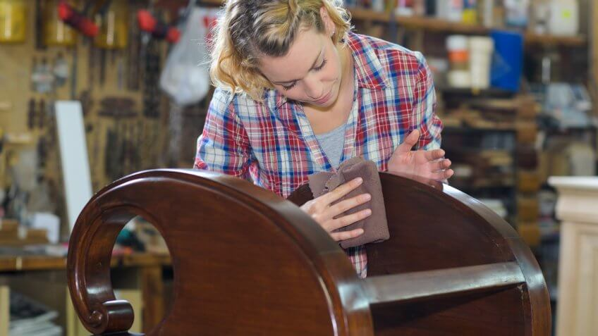woman polishing wooden object in workshop