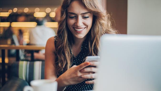 Smiling young woman with laptop and smart phone sitting in cafeteria, with copy space.