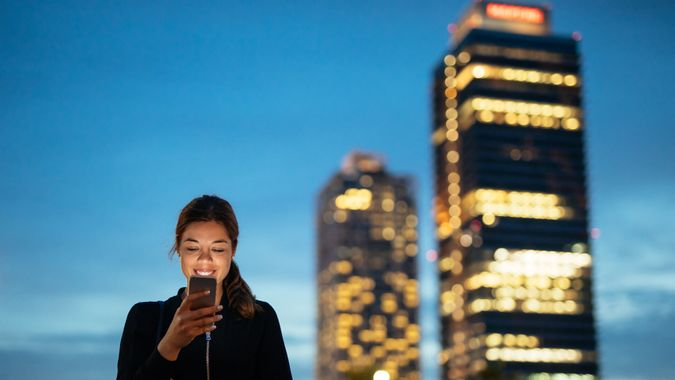 Portrait of a smiling young woman using mobile phone in the city in the evening.