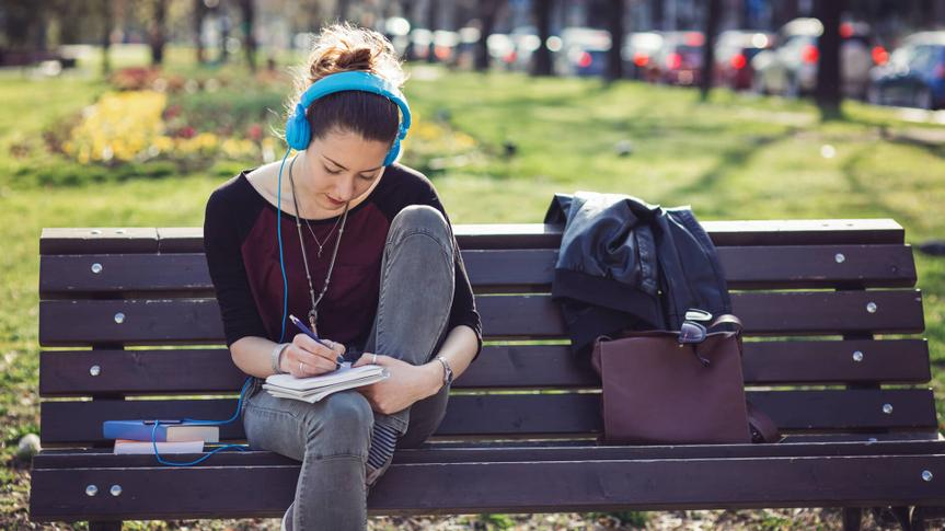 Student girl reading on a bench in the park and listening to music.