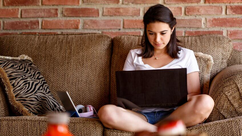 Hispanic young woman working on a laptop computer at home.