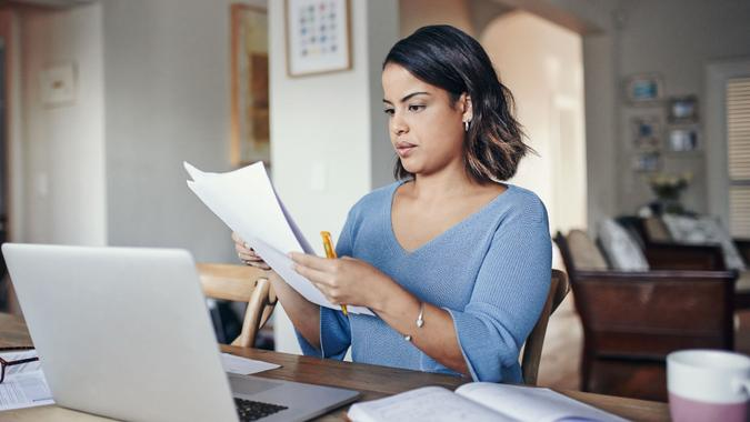 Shot of a young woman using a laptop and  going through paperwork while working from home.