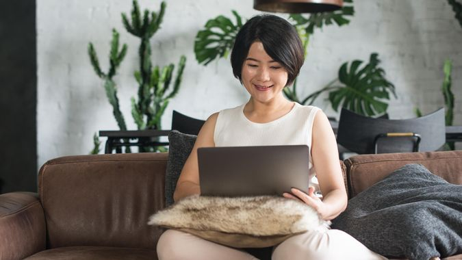 Young Asian woman using the laptop in the living room.