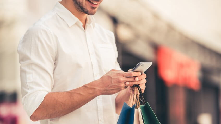 Guy with shopping bags is using a mobile phone and smiling while doing shopping in the mall.