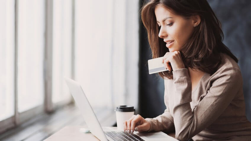 Young woman holding credit card and using laptop computer.