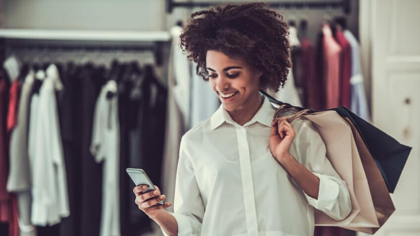 Girl is holding shopping bags, using a smart phone and smiling while doing shopping in female boutique.
