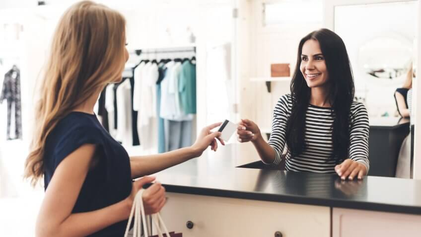 Can I pay with my card? Young woman with shopping bags giving her credit card to seller while standing at the clothing store.