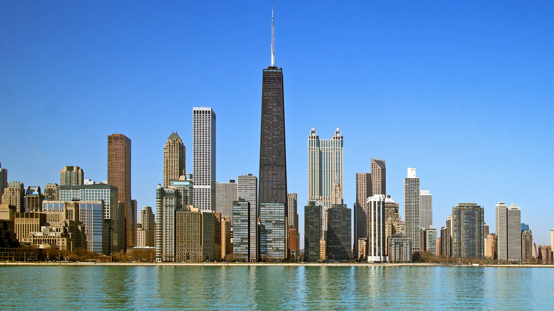 Day view of Chicago with buildings reflection on the water.