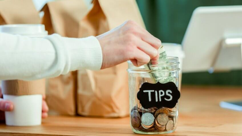 Unrecognizable coffee shop customer inserts cash into a tip jar at the checkout counter.