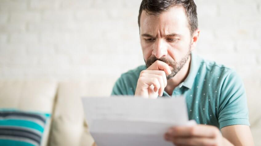 Close up shot of a young adult man reading the mail in the living room and worried about his credit card payments.