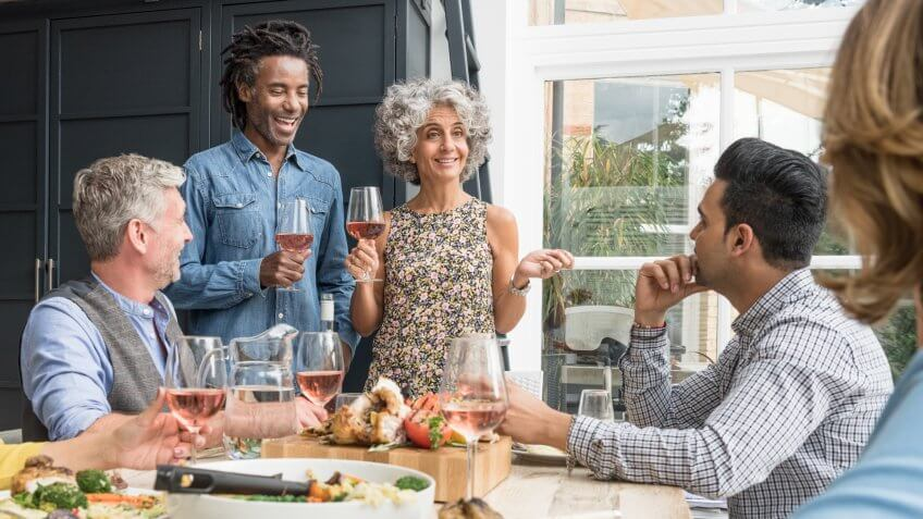 Group of friends having dinner party listening to man and woman holding rose wine.