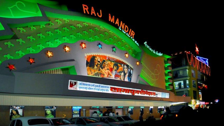 green lit movie theater raj mandir in jaipur, india, by night.