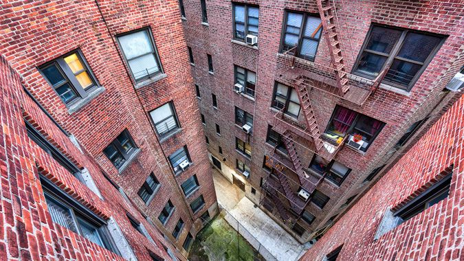 High angle, looking down view on illuminated brick apartment condo building architecture in Fordham Heights center, Bronx, NYC, Manhattan, New York City with fire escapes, windows.