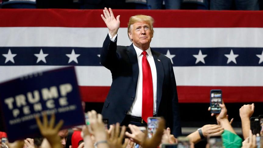 President Donald Trump waves hand at rally