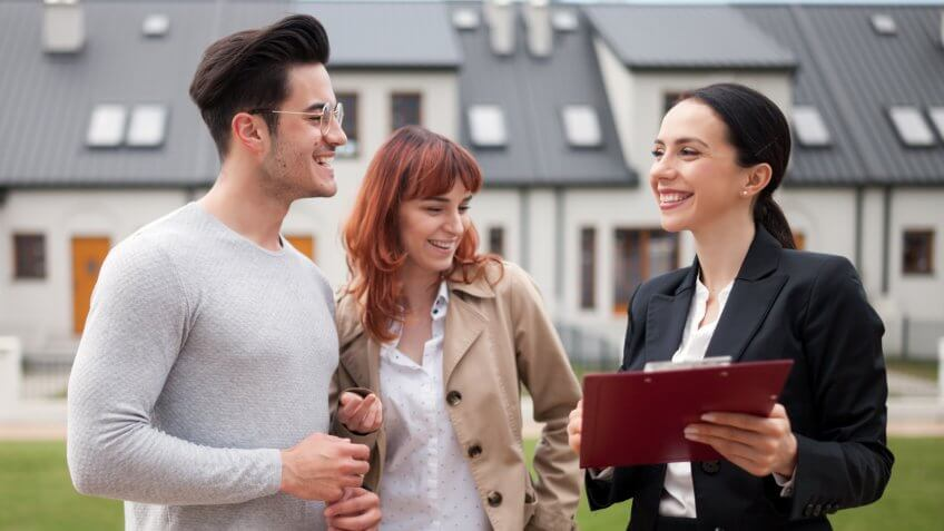 Real estate agent talking with young couple about buying new house