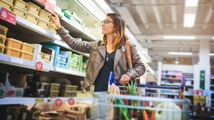 Shot of a young woman shopping at a grocery store.