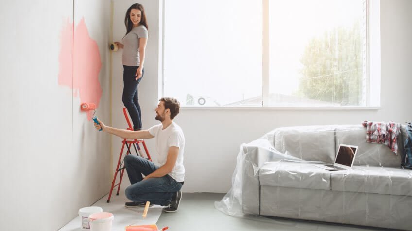 Young man and woman doing apartment repair together paint walls.