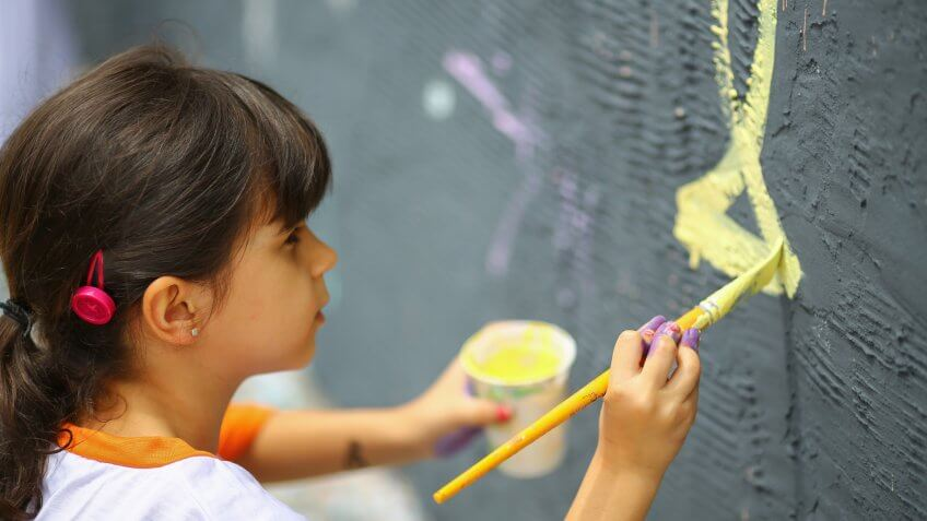 Young girl painting on wall mural