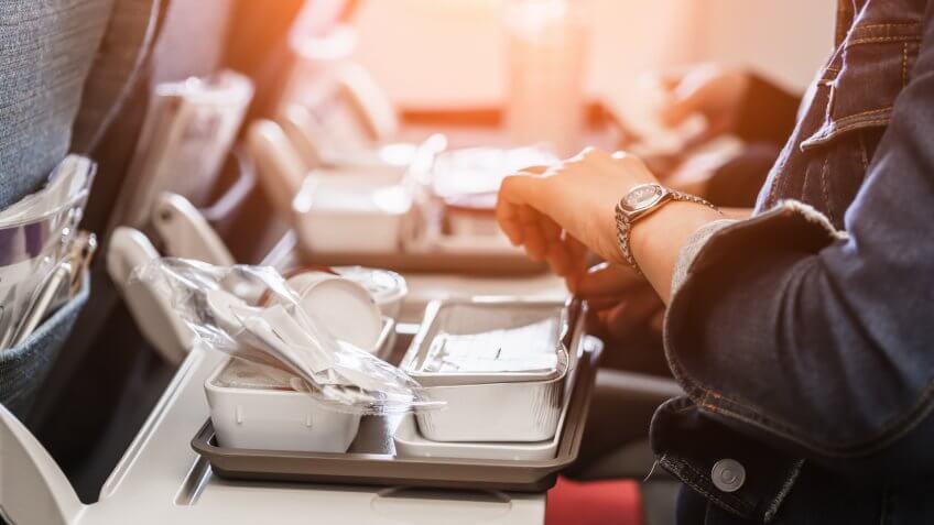 woman passengers eats lunch in travel aboard of international flight.