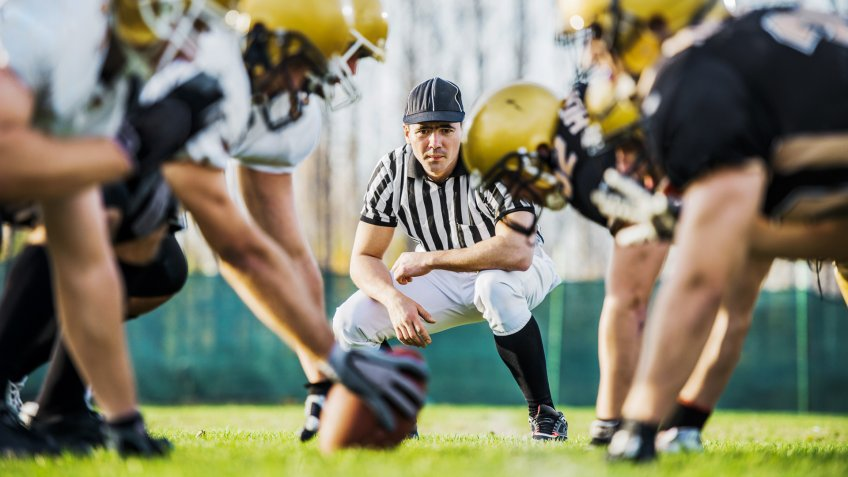 male football referee on line of scrimmage