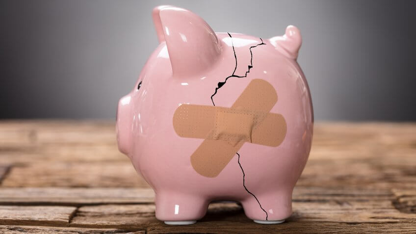 Closeup of broken pink piggybank with bandage on wood.
