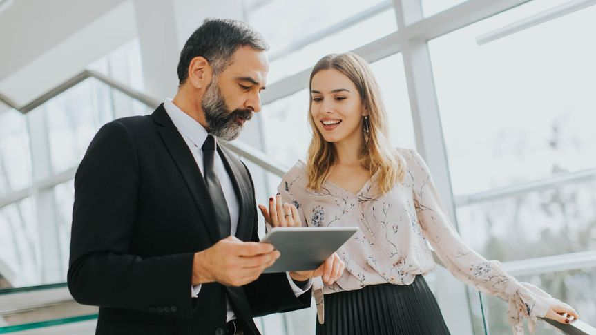 Portrait of business couple with digital tablet in office.