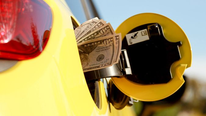 Mans Hand holding Cash while Refueling Vehicle.