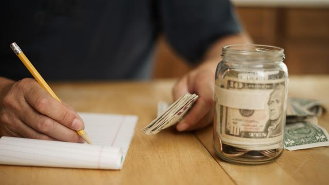 A male writes notes concerning money at the kitchen table.