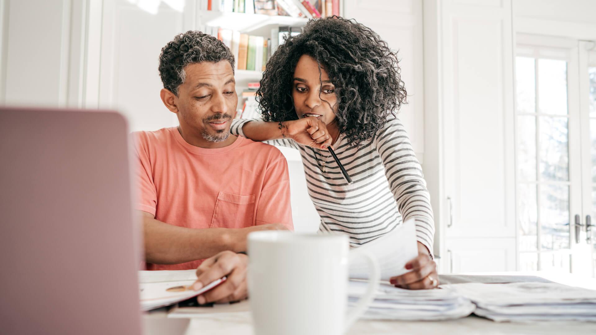 Couple and their financial planning in the kitchen with laptop.