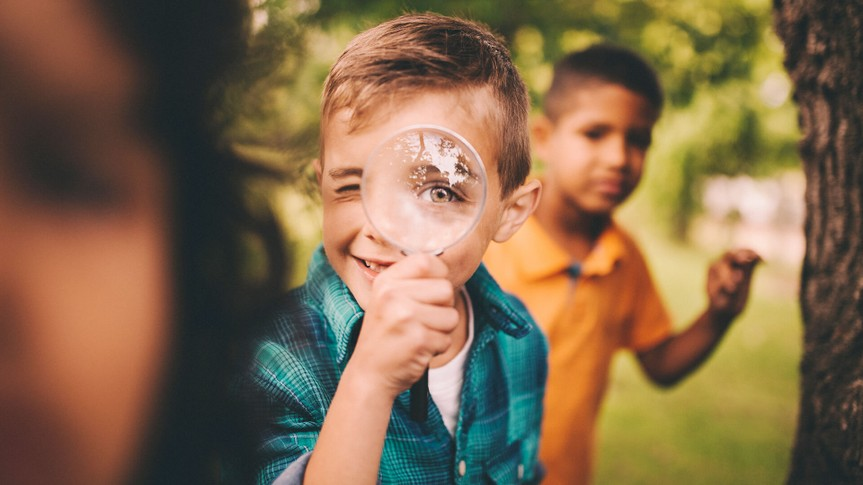 Portrait of a little boy holding up a large round magnifying glass to his face, making his eye look humourously large, while playing with friends in a summer park.