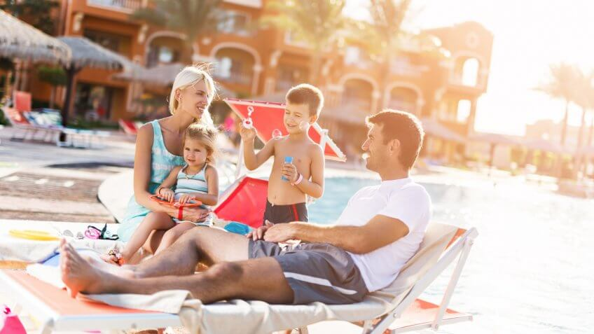 Happy mid adult parents enjoying with their little children at the poolside during summer day.