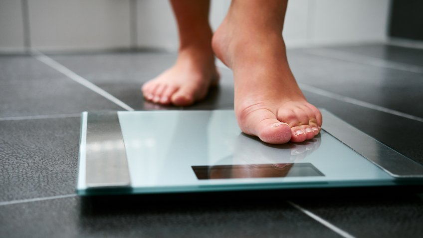 Female bare feet with weight scale in the bathroom.