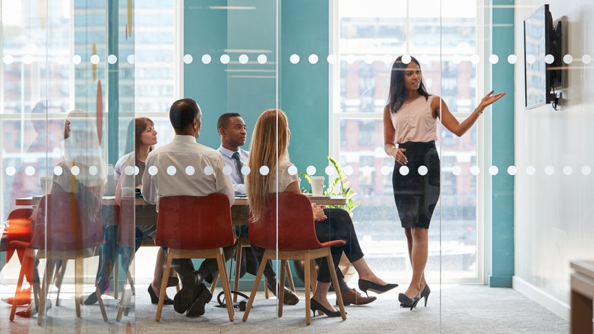 Female boss shows presentation on screen at business meeting.