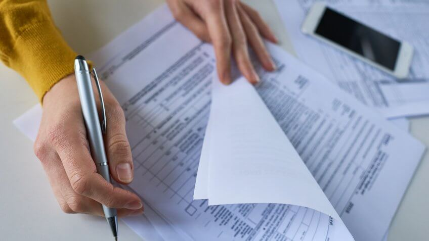 Close-up of unrecognizable woman attentively examining business documents and making correction at table.