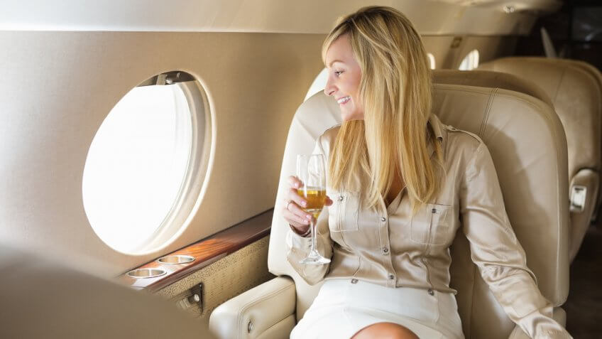 Pretty professional woman drinking champagne on board private jet.