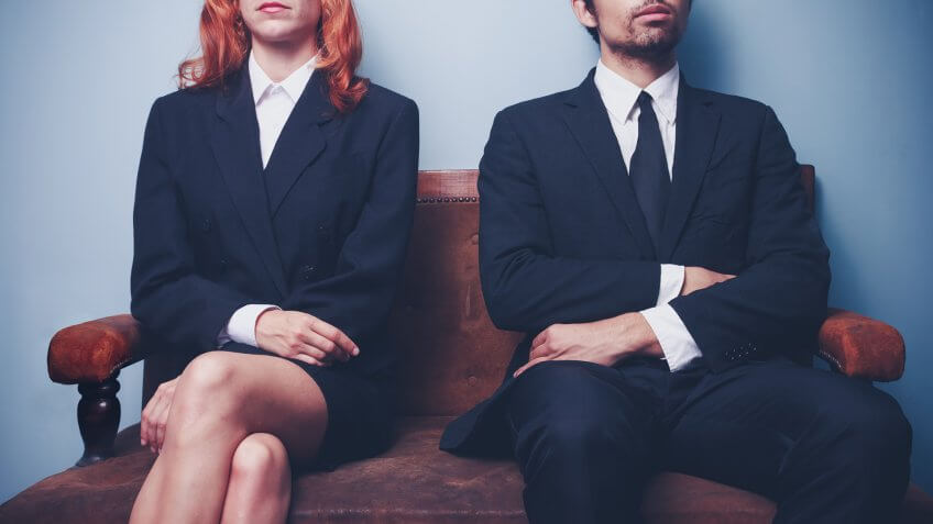 Two sharply dressed business people are waiting on a sofa with a serious expression on their faces.