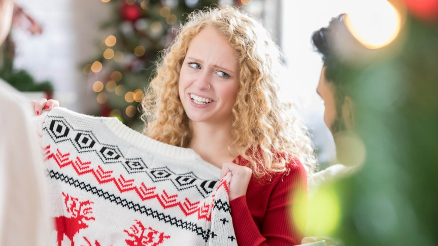 Young Caucasian woman makes a face while holding an ugly Christmas sweater.