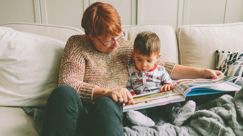 grandparent with child reading book.