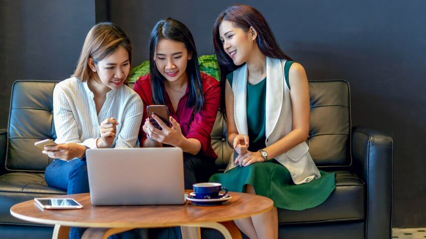 Group of charming beautiful Asian women using smartphone and laptop, chatting on sofa at cafe, modern lifestyle with gadget technology or working woman on casual business concept.