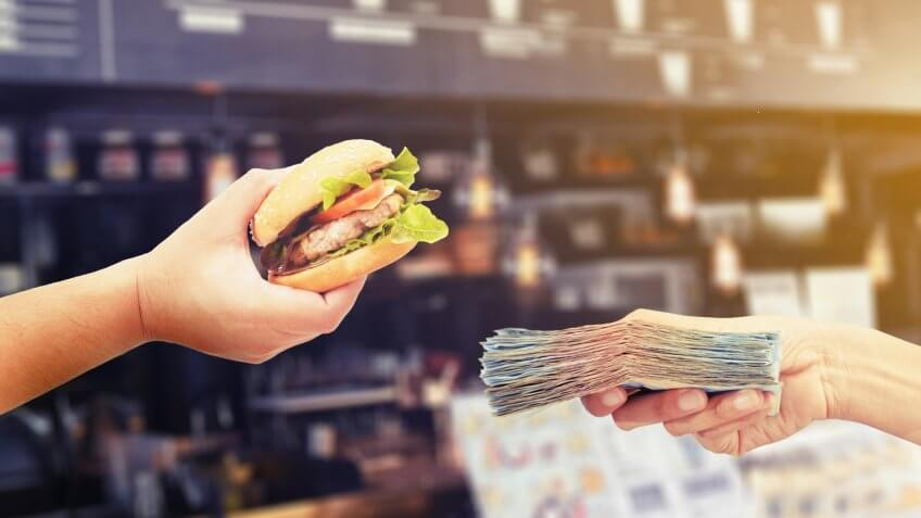 hands holding burger and cash