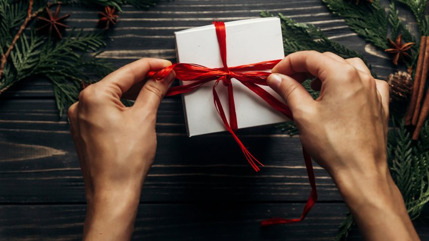 hands wrapping christmas present with red ribbon on stylish wooden background flat lay with green branches.