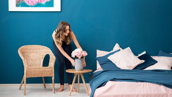 Young woman decorating bedroom with beautiful flowers at home.
